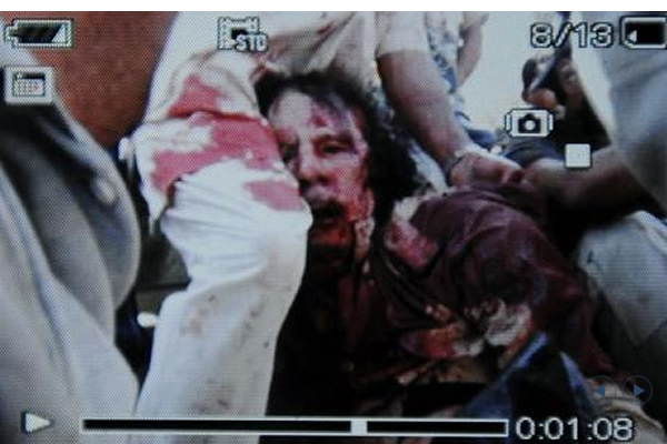 He's not walking, he's not walking, he's not walking anymore... Dead man dead Colonel Gaddafi