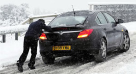 A man tries to get his car moving in the snow