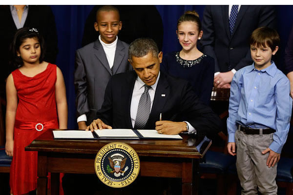 President Obama puts pen to paper on gun control legislation