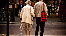 An elderly couple wait to cross the road