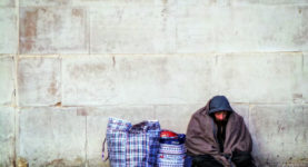 A homeless person sheltering under a concrete wall