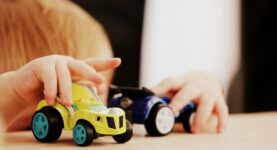 child at table playing with toy cars - Photo by Sandy Millar on Unsplash