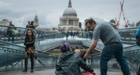 Man helps homeless person by London's Millenium Bridge - Photo by Tom Parsons on Unsplash