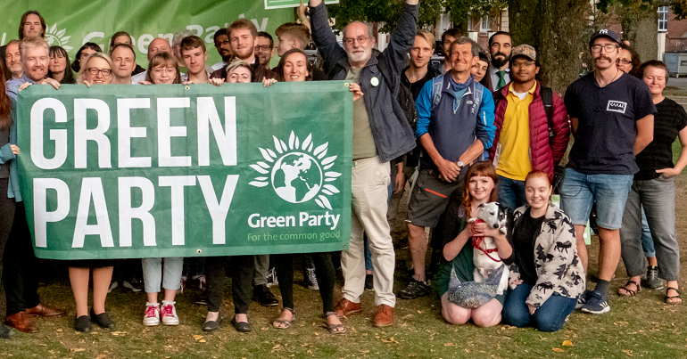 Green Party activists standing with a party banner