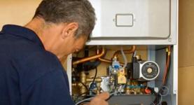 A mechanic repairing a boiler